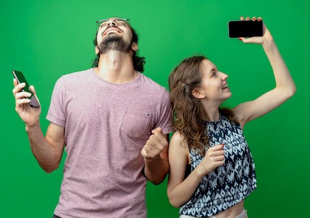 Giovane coppia uomo e donna felice ed eccitato tenendo i loro smartphone stringendo i pugni in piedi sopra il muro verde