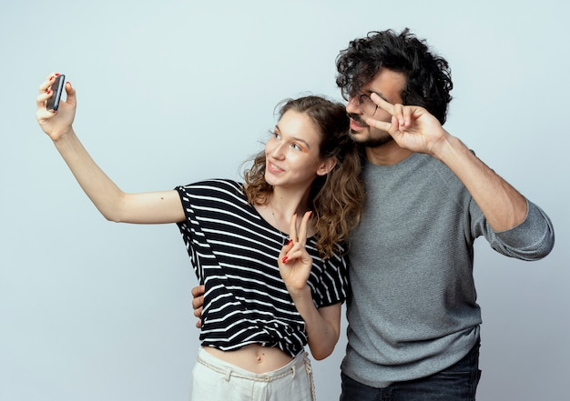 Coppia giovane uomo e donna felice in amore, donna felice di scattare una foto di loro utilizzando lo smartphone in piedi su sfondo bianco