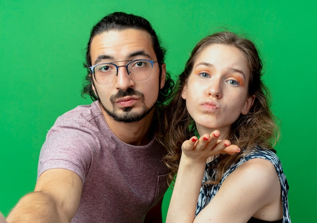 Young couple man and woman happy in love , woman blowing a kiss with hand in front of her over green wall