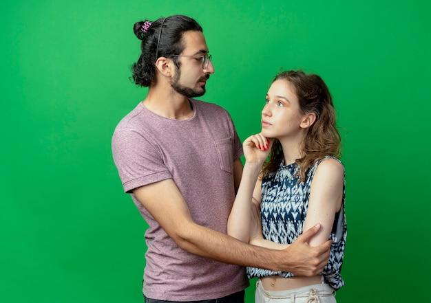 Giovane coppia uomo e donna uomo felice che abbraccia la sua ragazza mentre lei in piedi con espressione pensierosa sul muro verde
