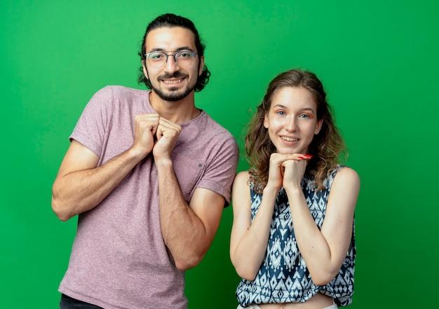Giovane coppia uomo e donna, felice e positivo mano nella mano insieme in attesa di sorpresa in piedi oltre il muro verde