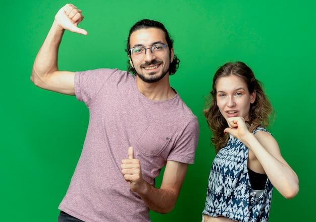Giovane coppia uomo e donna, felice e positivo che punta a se stessi in piedi oltre il muro verde
