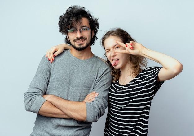 Coppia giovane uomo e donna donna felice e positiva stiking fuori la lingua che mostra il segno di vittoria in piedi su sfondo bianco