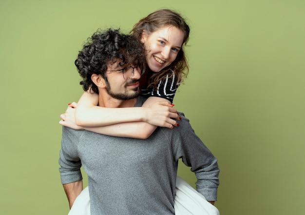 Coppia giovane uomo e donna divertirsi insieme, uomo che porta la sua ragazza sulla schiena su sfondo verde