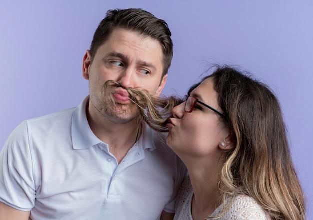 Giovane coppia uomo e donna che hanno divertimento insieme in piedi sopra la parete blu