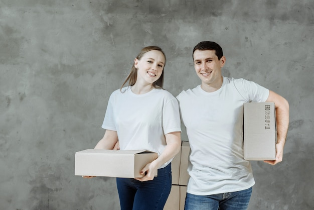 Young couple man and woman holding boxes for moving in a new house