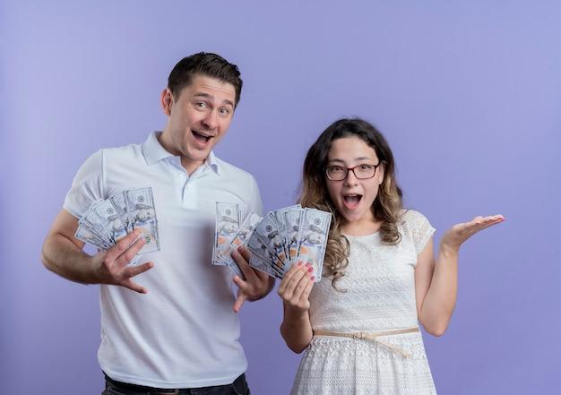 Giovani coppie uomo e donna che tengono contanti felici e sorpresi che stanno insieme sopra la parete blu