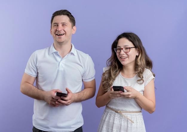 Coppia giovane uomo e donna che tengono smartphone felice e sorridente positivo allegramente in piedi insieme sopra la parete blu