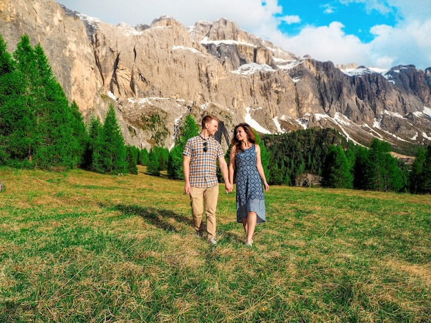 Young couple man and woman hugs and walks on the lawns in dolomites, italy