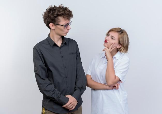 Giovane coppia uomo e donna guardando l'altro con espressione scettica in piedi sopra il muro bianco