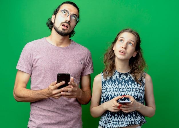 Giovane coppia uomo e donna, alzando lo sguardo perplesso mentre si tengono gli smartphone in piedi sopra il muro verde