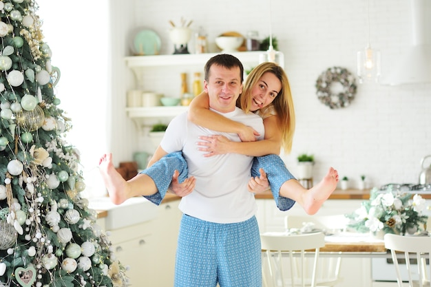A young couple-a man and a woman in pajamas hugging and fooling around on the background of a modern kitchen and a christmas tree.