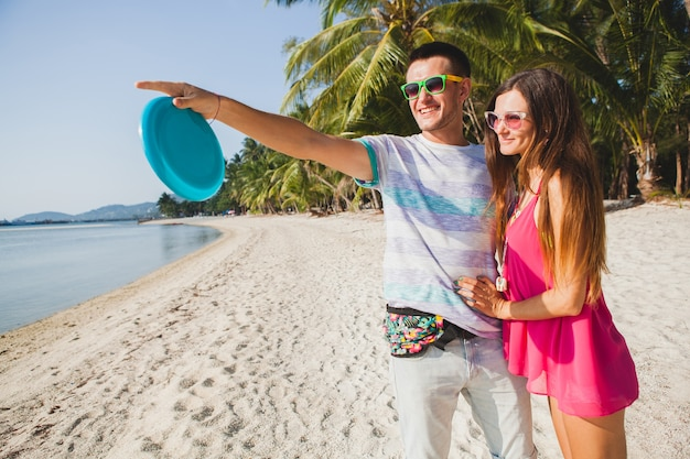 Young couple man and woman playing flying disk on tropical beach, summer vacation, love, romance, happy mood, smiling, having fun, hipster outfit, sunglasses, denim shorts, sunny, positive mood