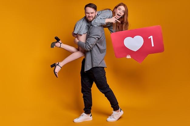 オレンジ色の背景に分離されたサインのようなポーズで若いカップルの男性女性。コピースペースをモックアップします。