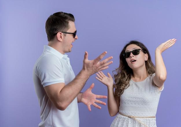 Coppia giovane uomo e donna che litigano gesticolando con le mani sul blu