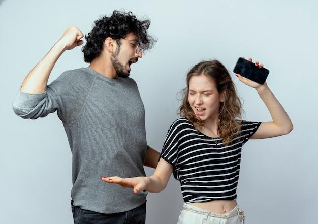 Giovane coppia uomo e donna che litigano gridando a vicenda in piedi sopra il muro bianco