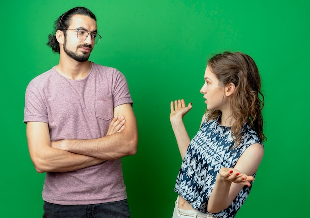 Giovane coppia uomo e donna che litigano, donna sconvolta parlando con il suo fidanzato con in piedi con le braccia incrociate accigliato sul muro verde