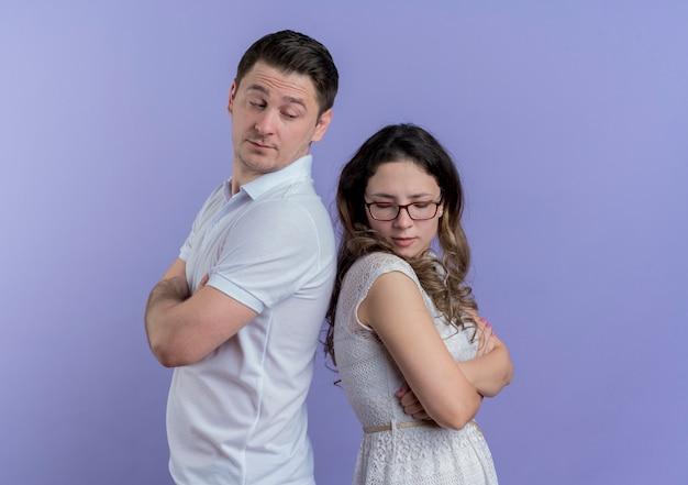 Coppia giovane uomo e donna in piedi schiena contro schiena dopo la lotta per il muro blu