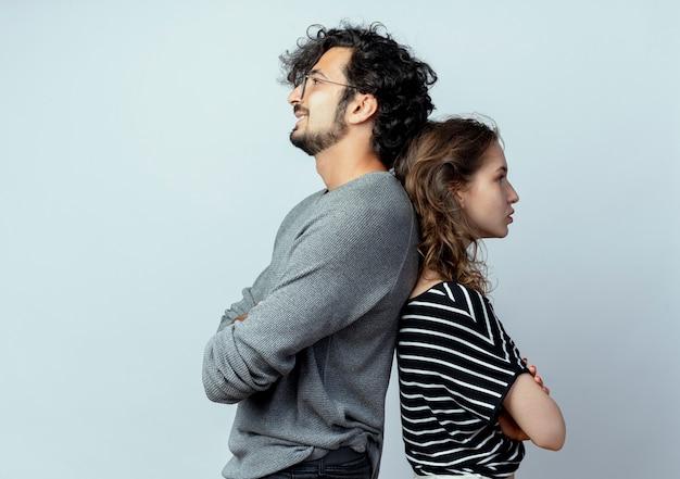 Giovane coppia uomo e donna in piedi schiena contro schiena sul muro bianco