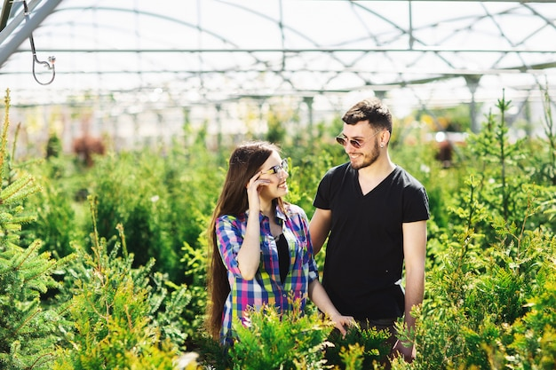 Young couple, man and woman, standing together in the garden center and choose plants