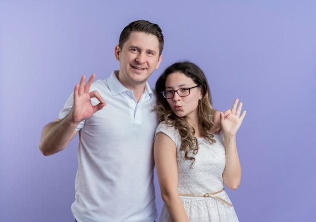 Giovane coppia uomo e donna in piedi insieme mostrando ok canta sorridendo oltre la parete blu
