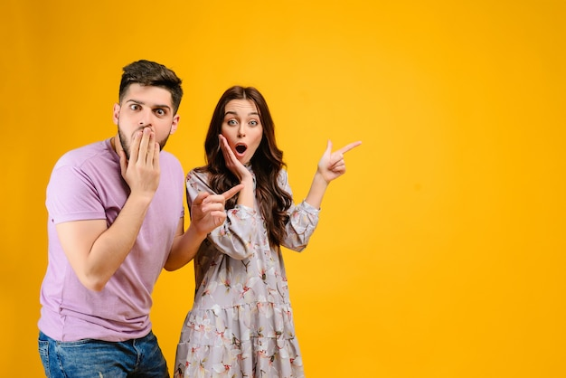 Young couple man and woman surprised pointing at copyspace