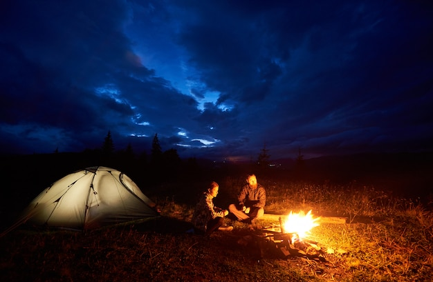 Young couple man and woman tourists enjoying at night camping in the mountains, sitting near burning campfire and illuminated tourist tent under beautiful evening cloudy sky