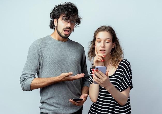 Coppia giovane uomo e donna, uomo sconvolto che punta alla sua ragazza che tiene lo smartphone in piedi su sfondo bianco