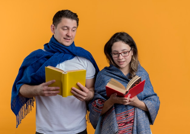 Young couple man and woman with blankets holding books happy and positive smiling standing over orange wall