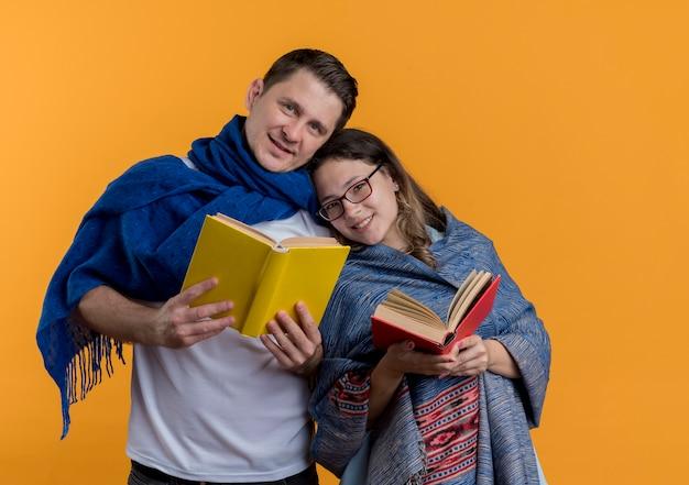 Giovane coppia uomo e donna con coperte in possesso di libri sorridenti felici e positivi che stanno insieme sopra la parete arancione