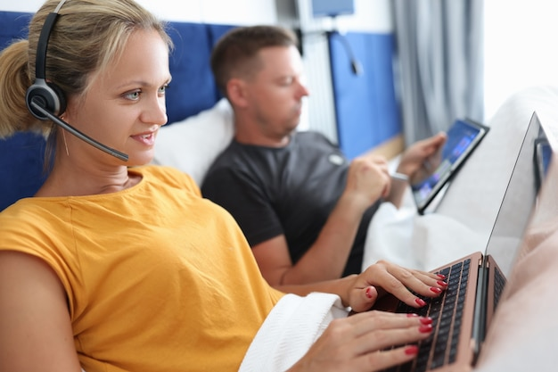Young couple man and woman work remotely on laptop while lying in bed freelance work concept