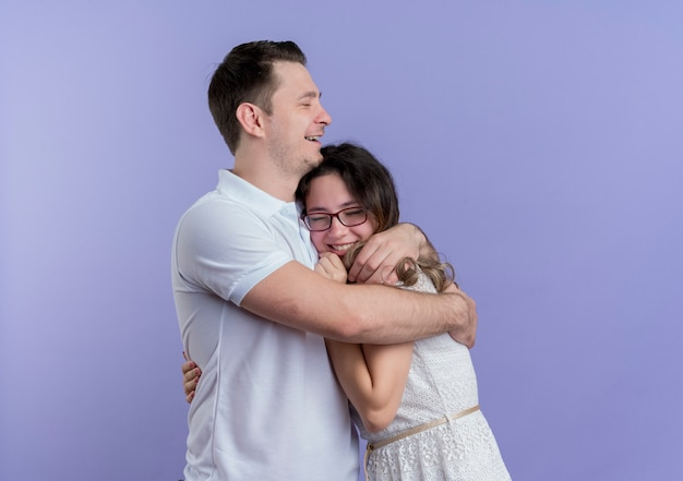 Giovane coppia uomo e donna felice nell'amore che abbraccia sopra l'azzurro