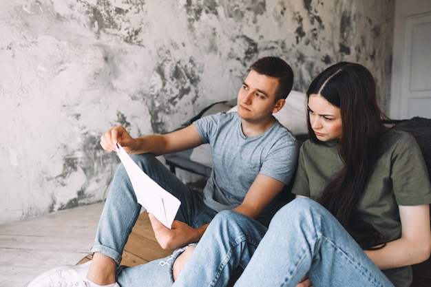A young couple manages finances by looking through their bank accounts