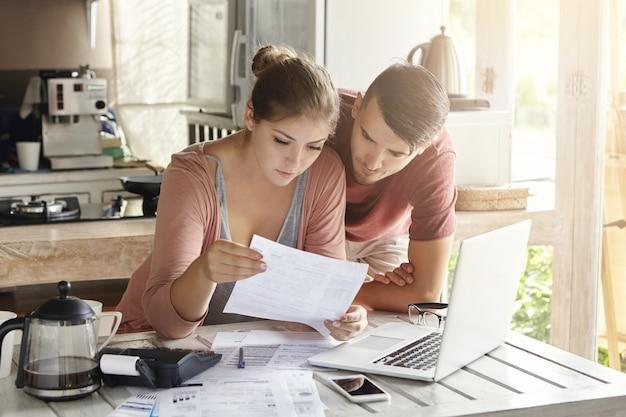 若いカップルが財政を管理し、モダンなキッチンでラップトップコンピューターと電卓を使用して銀行口座を確認します。女と男が一緒に事務処理を行う