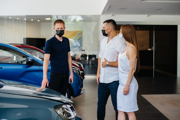 Young couple in masks selects a new vehicle and consult with a representative of the dealership i