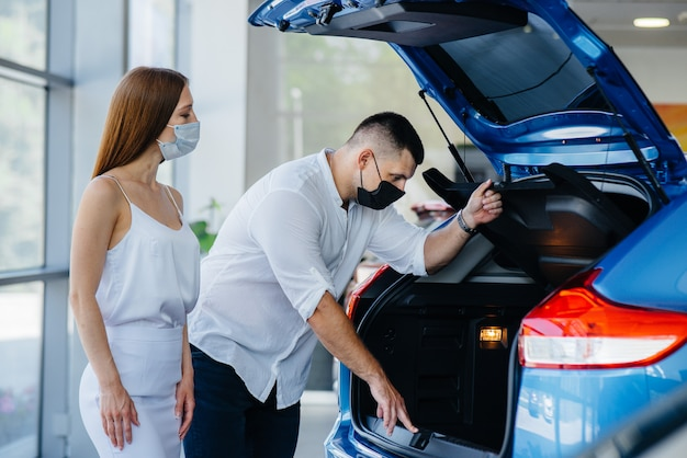 Young couple in masks selects a new vehicle and consult with a representative of the dealership in the period of the pandemic. car sales, and life during the pandemic.