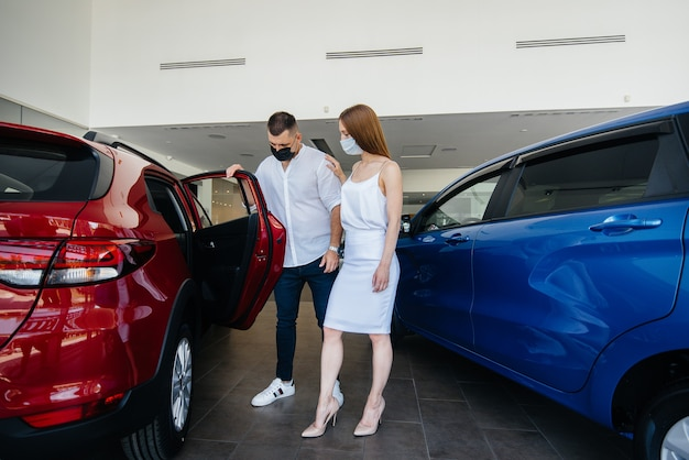 Young couple in masks selects a new vehicle and consult with a representative of the dealership in the period of the pandemic.