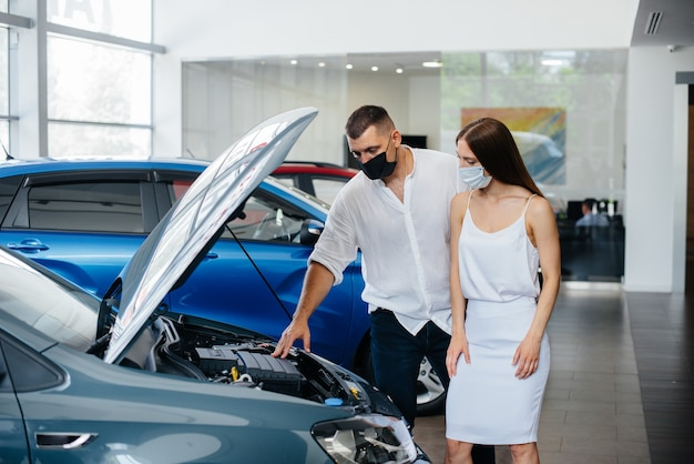 Young couple in masks selects a new vehicle and consult with a representative of the dealership in the period of the pandemic