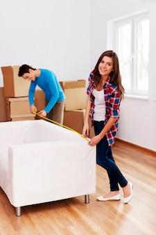 Giovani coppie che misurano il divano nel loro nuovo appartamento