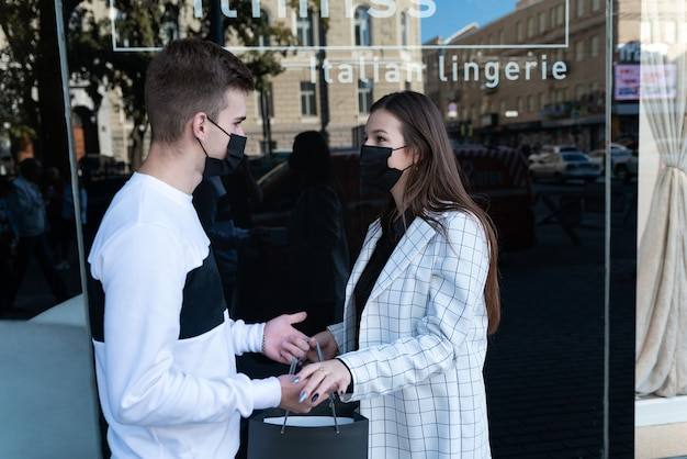 Young couple in medical masks with purchases on shop windows background. shopping during quarantine.
