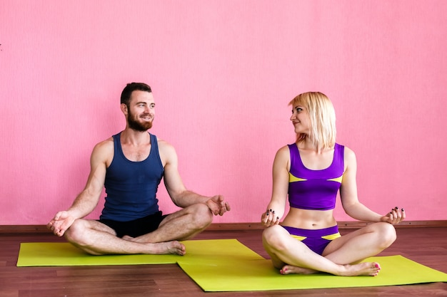 Young couple meditating in lotus position.