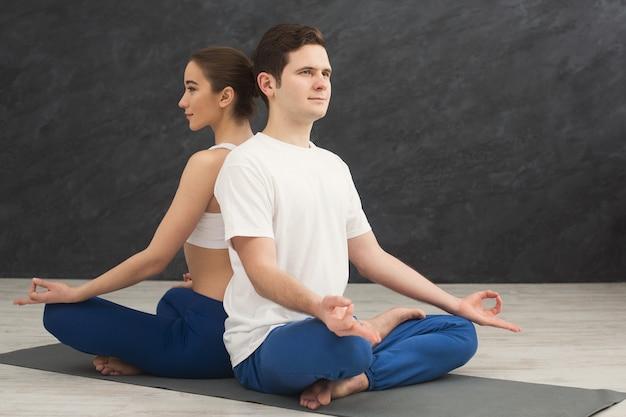 一緒に瞑想する若いカップル。マットの上に蓮華座で背中合わせに座っている男女、コピースペース