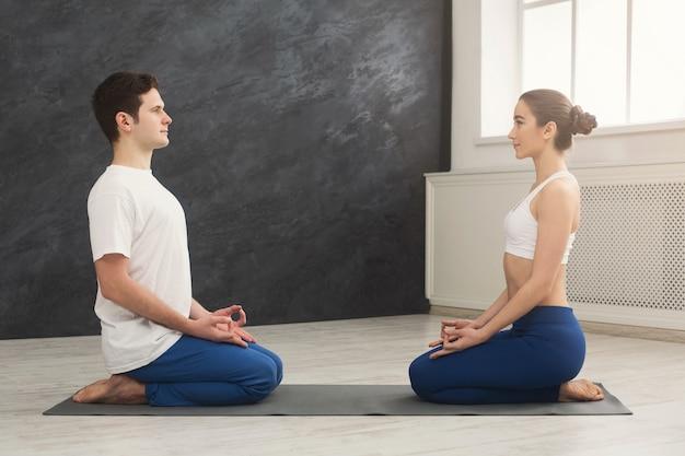 一緒に瞑想する若いカップル。マットの上に向かい合って座っている男女、コピースペース