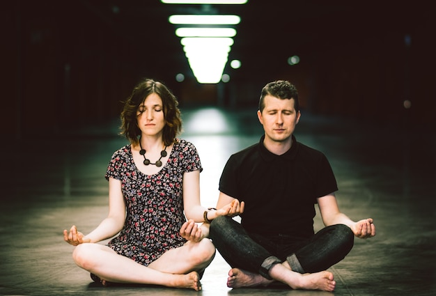 Young couple meditating together sitting in the parking lot.