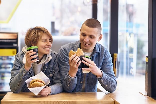 若いカップルはハンバーガーを食べるためにファーストフードで会った
