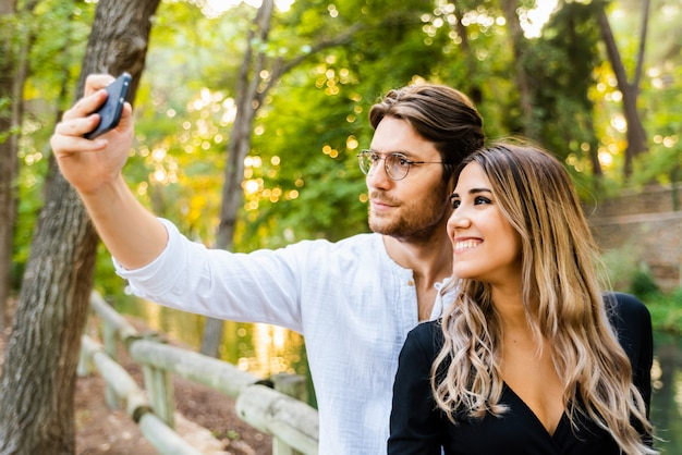 A young couple of models celebrate their love and happiness with a selfie to share on social networks.