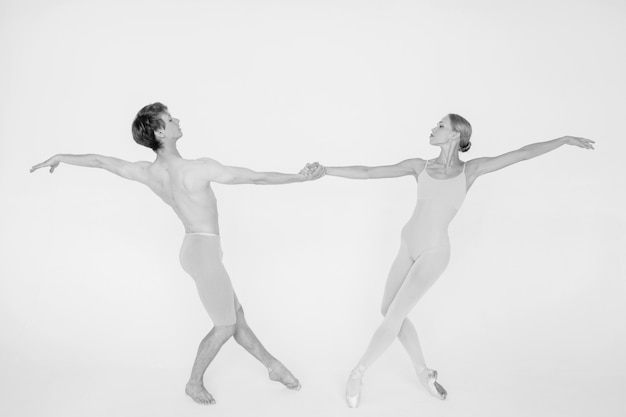 Young couple of modern ballet dancers posing over white studio background
