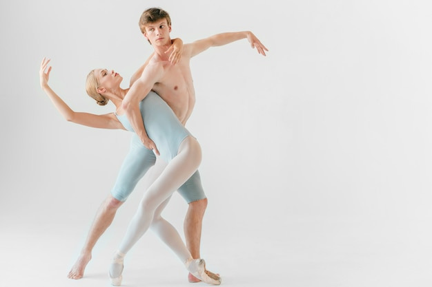 Young couple of modern ballet dancers training in studio.