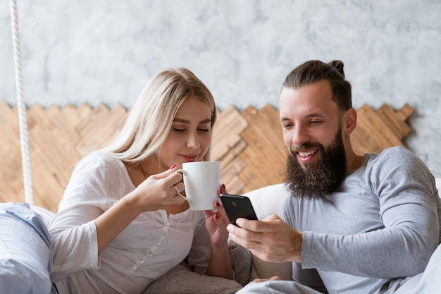 Молодая пара утренний ритуал. планы обсуждаем. женщина с чашкой любимого напитка комфорта и мужчина со смартфоном.