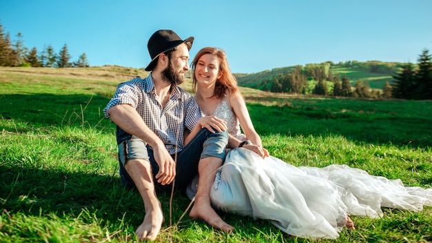 A young couple in the mountains are sitting on the grass
